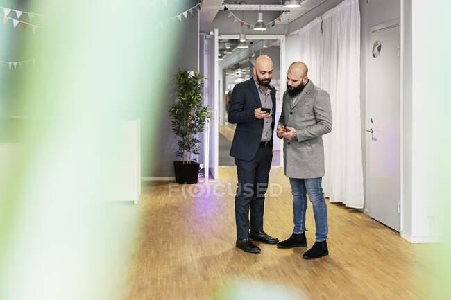 Männer, die im Büro auf das Smartphone schauen, ganzseitige Ansicht — Stockfoto