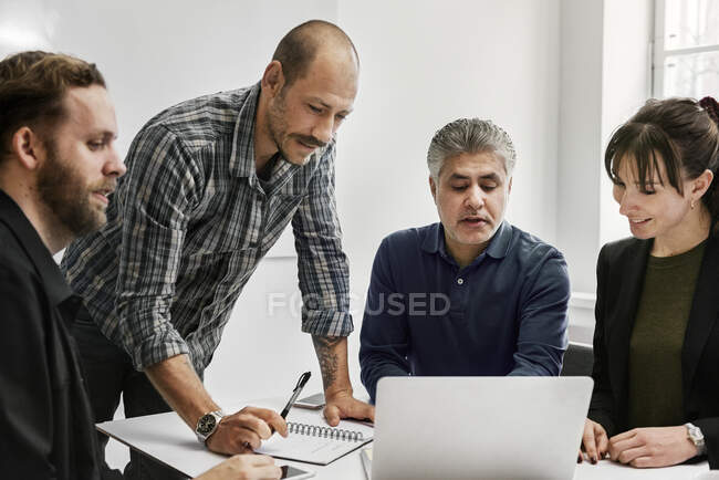 Businesspeople using laptop and working together in office — Stock Photo