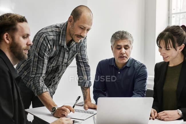 Les hommes d'affaires utilisant un ordinateur portable et travaillant ensemble dans le bureau — Photo de stock