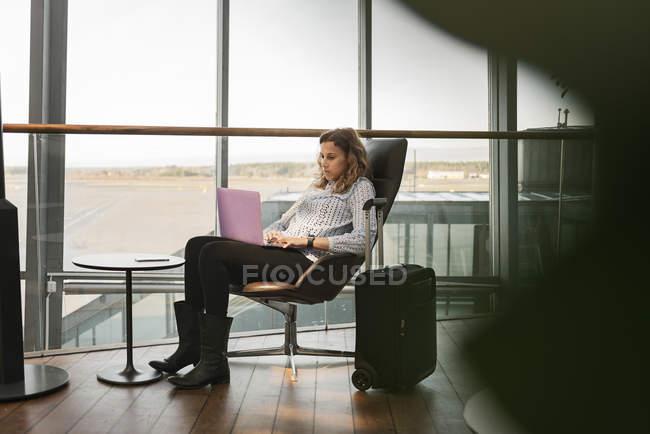 Donna che utilizza il computer portatile in aeroporto — Foto stock