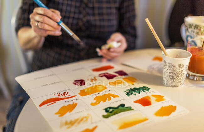 Woman painting with watercolors, cropped shot — Stock Photo