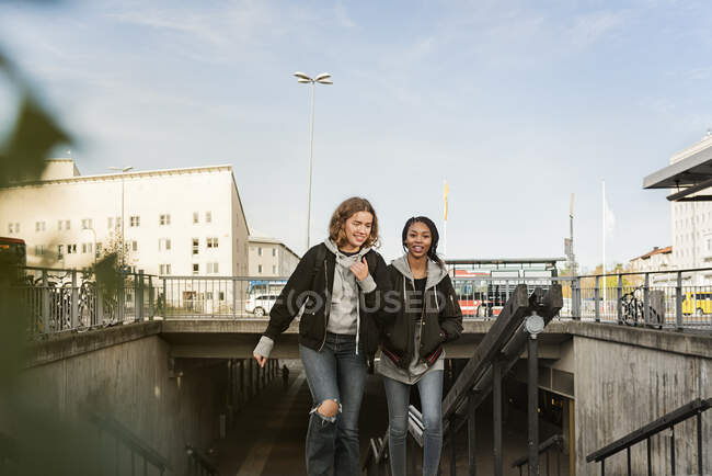 Teenage girls walking and smiling in city — Stock Photo