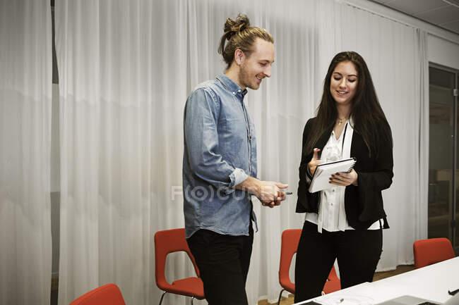 Sorridendo giovani colleghi che parlano in ufficio — Foto stock