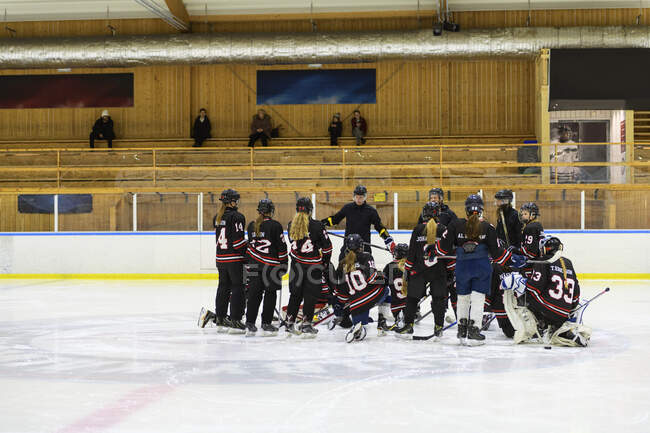 Les filles écoutent leur entraîneur pendant l'entraînement de hockey sur glace — Photo de stock