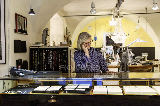 Goldsmith taking phone call at counter of store — Stock Photo