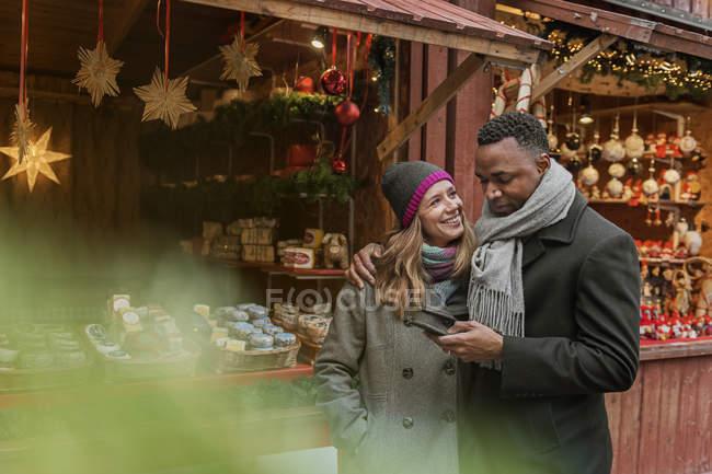 Coppia utilizzando smartphone e sorridente, messa a fuoco selettiva — Foto stock