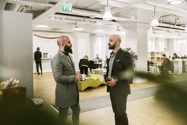 Vue latérale d'hommes barbus sérieux tenant des tasses et parlant au bureau — Photo de stock