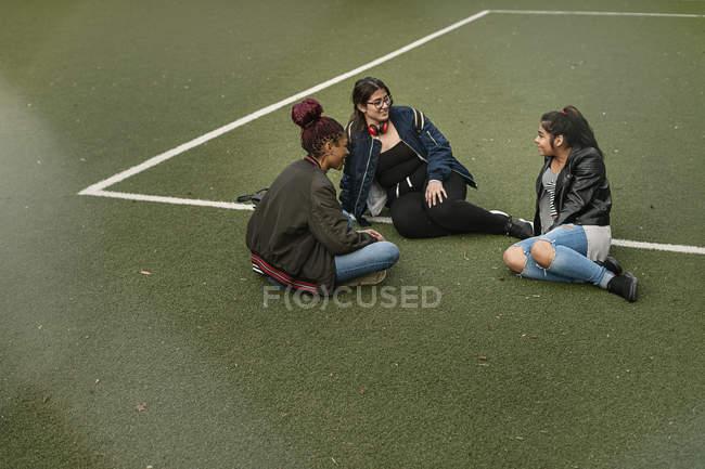 Teenage girls sitting on tennis court — Stock Photo