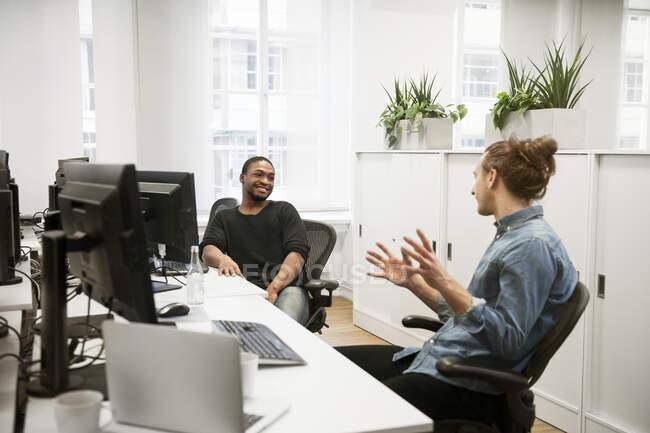 Compañeros de trabajo jóvenes sentados en la mesa y hablando en la oficina - foto de stock