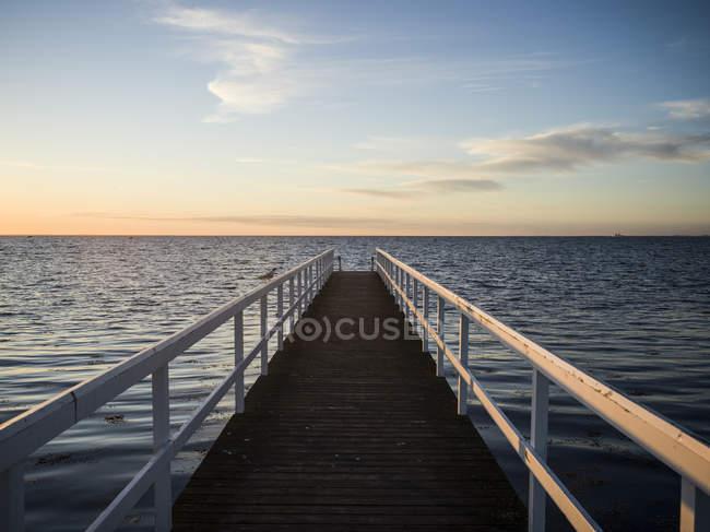 Vue panoramique sur la jetée et la mer au coucher du soleil — Photo de stock