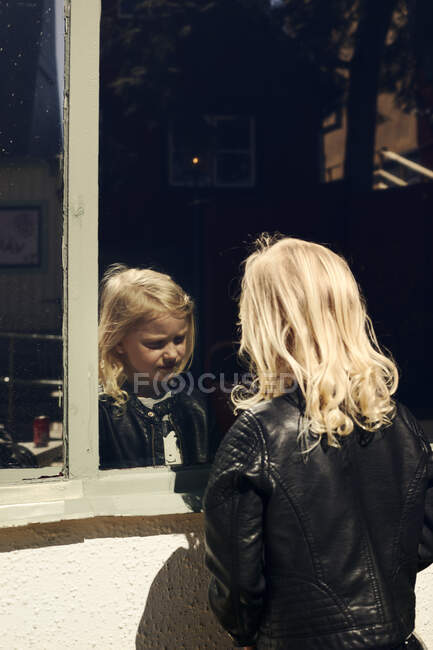 Girl and her reflection in window — Stock Photo