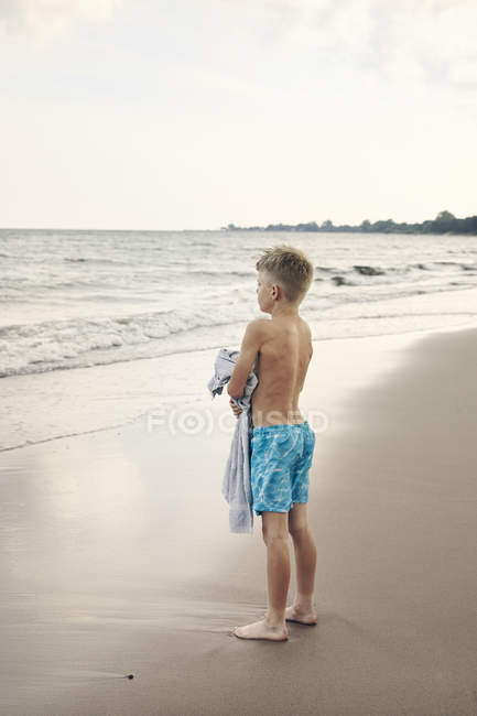 Junge trägt Handtuch am Strand — Stockfoto