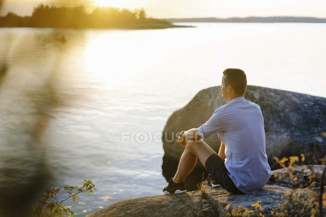 Man sitting on rock by sea, selective focus — Stock Photo
