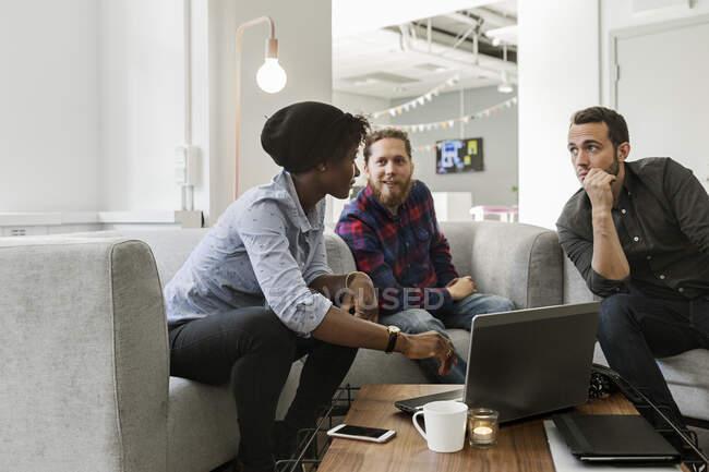 Collègues utilisant un ordinateur portatif et discutant du travail au bureau — Photo de stock