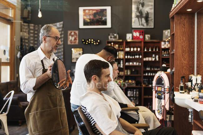 Barbier montrant au client son reflet dans le miroir — Photo de stock