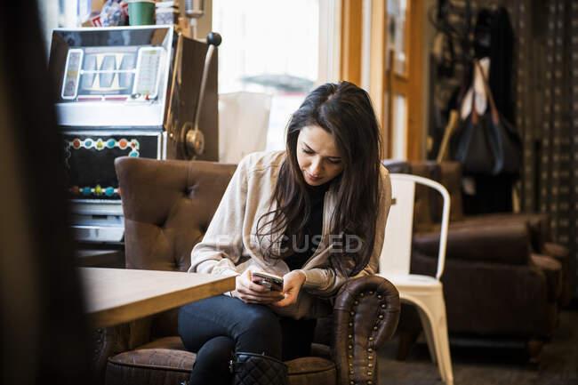 Mujer joven sentada a la mesa en la barbería - foto de stock