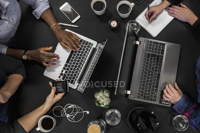 Coworkers with laptops and smartphones working at table, partial top view — Stock Photo