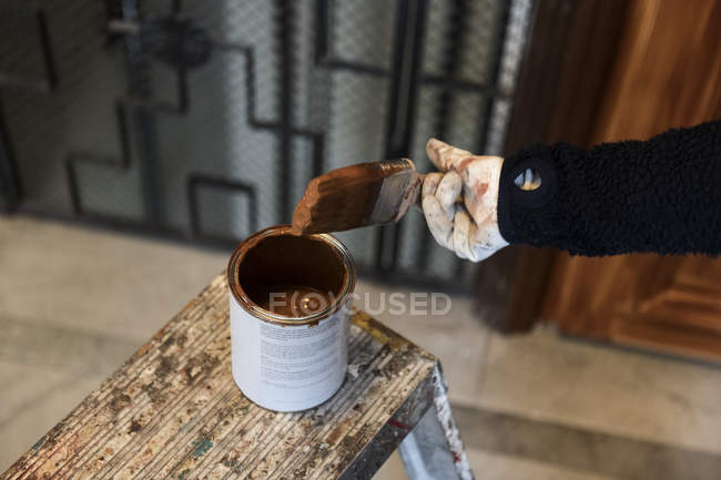Hand of painter dipping paintbrush into paint can — Fotografia de Stock