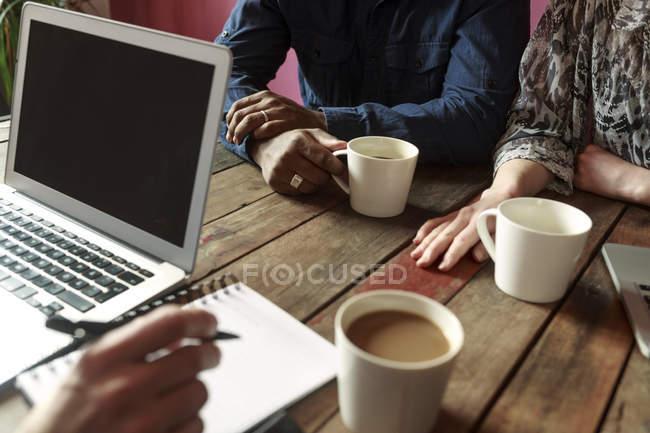 Armas de empresarios sobre la mesa durante la reunión - foto de stock