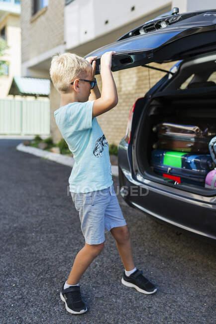 Boy closing car boot, full length view — Stock Photo