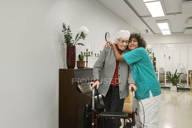Nurse hugging senior woman — Stock Photo
