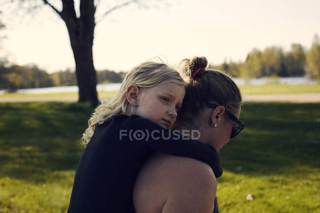 Mid adult woman giving girl piggyback in park — Stock Photo