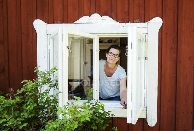 Maduro mulher olhando para fora janela e sorrindo no câmara — Fotografia de Stock