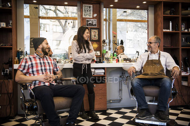 Peluqueros sonriendo y mirándose en la barbería - foto de stock
