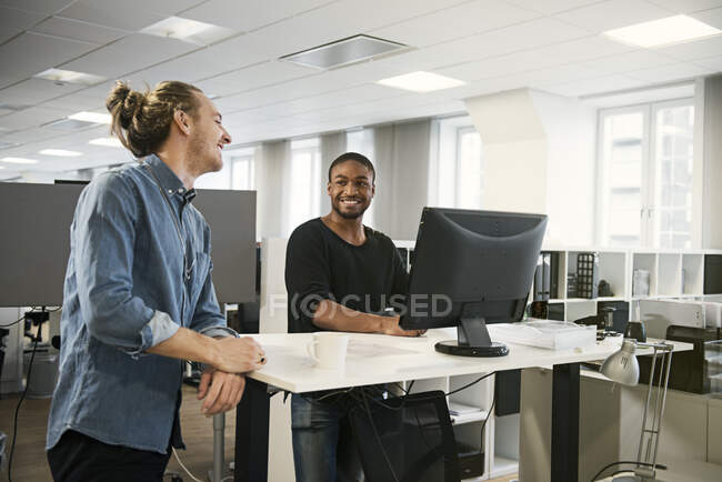 Smiling male coworkers talking at desk in office — Stock Photo