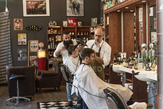 El peluquero que seca los cabellos del hombre joven en la barbería - foto de stock