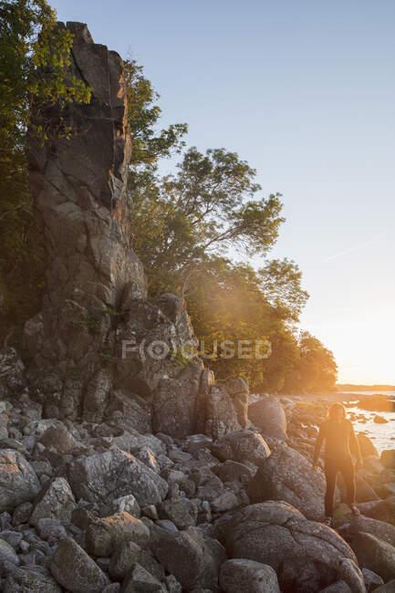 Silhueta do homem andando sobre pedras ao pôr do sol — Fotografia de Stock