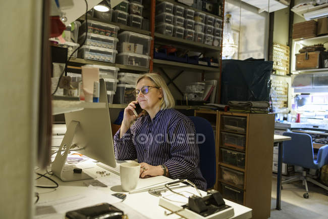 Goldsmith taking phone call and using computer — Stock Photo