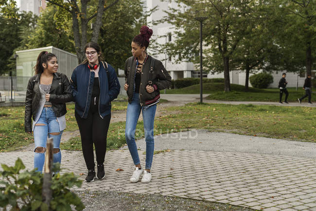 Teenage girls walking in park, selective focus — стокове фото
