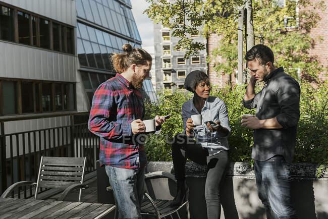 Des amis tenant des tasses de café à l'extérieur par une journée ensoleillée — Photo de stock