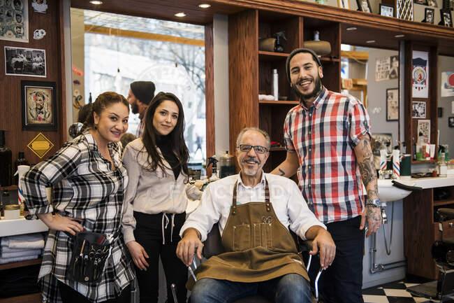 Retrato de barberos sonriendo a la cámara en la barbería - foto de stock