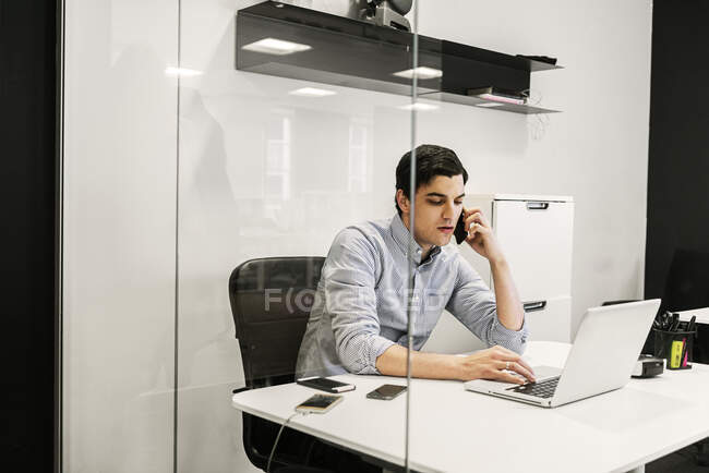 Young man using laptop while talking on phone in office — Stock Photo