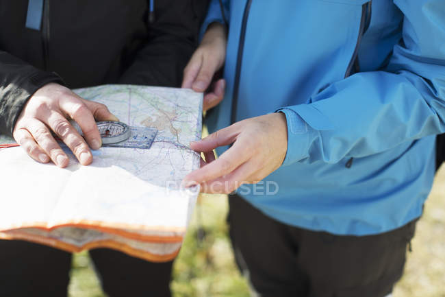 Women using compass and map, cropped view — Stock Photo