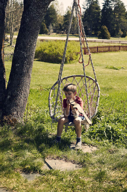 Boy sitting on chair hanging from tree — Stock Photo