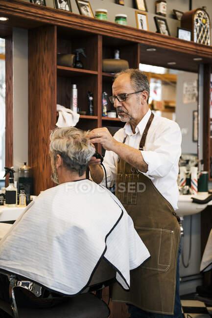 Barber cutting customer hair in barbershop — Stock Photo