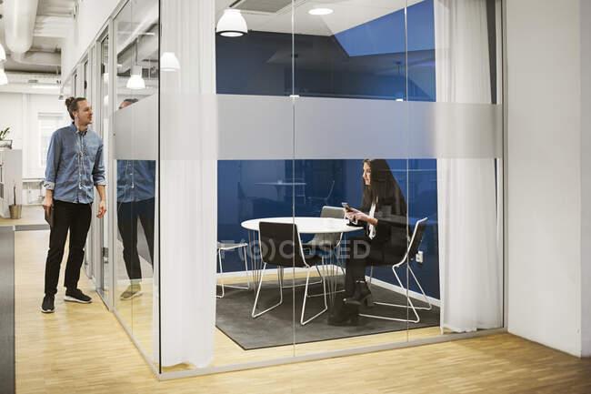 Giovani colleghi di sesso maschile e femminile che utilizzano smartphone e lavorano in ufficio — Foto stock
