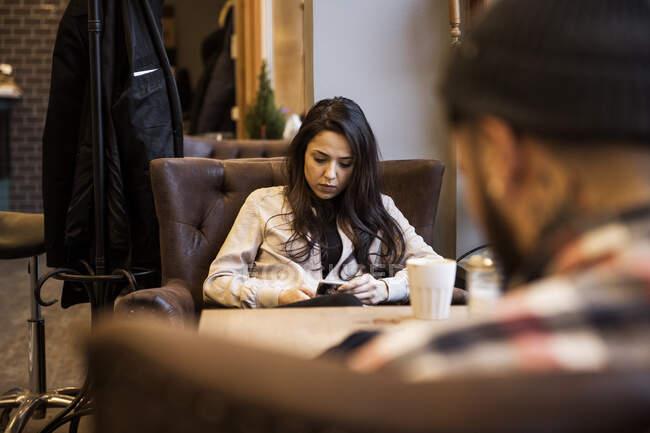 Jeune femme assise à table dans un salon de coiffure — Photo de stock