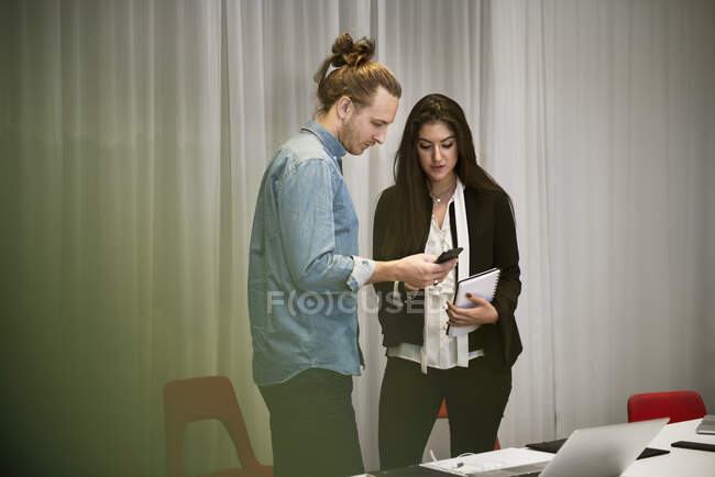 Young male and female coworkers discussing work in office — Stock Photo