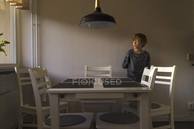 Хлопчик стоїть за столом, вибірковий фокус — стокове фото