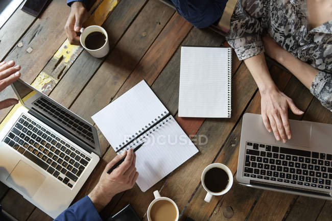 Arms of businesspeople on office table during meeting — Stock Photo