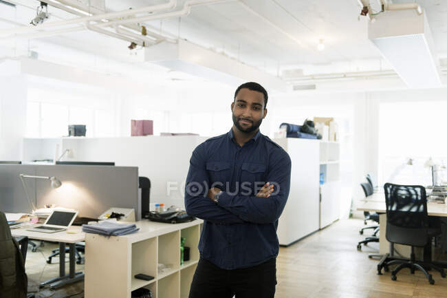 Portrait of businessman standing with crossed arms and looking at camera in office — Stock Photo