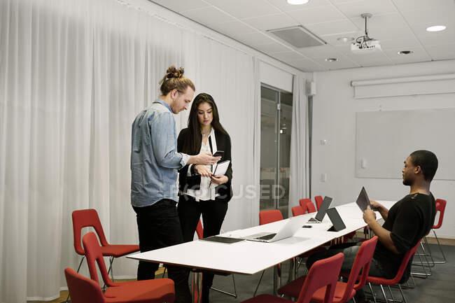 Des gens d'affaires utilisant des dispositifs numériques pendant une réunion au bureau — Photo de stock