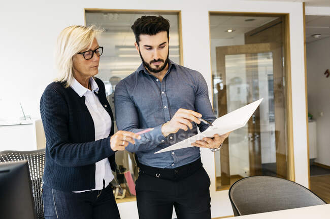 Business people with folder discussing work in office — Stock Photo