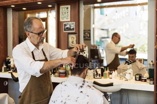 Парикмахер стрижет волосы молодого человека, избирательное внимание — стоковое фото