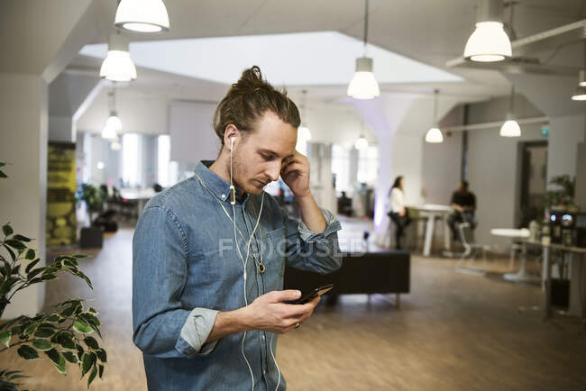 Focused young man using earbuds with smartphone in office — Stock Photo