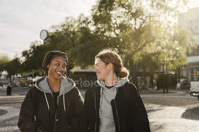 Teenage girls smiling and walking on street — Stock Photo